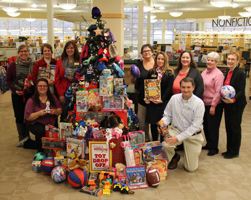 Harford County Public Library employees gather to give donation of toys collected from Library staff and customers to The Aegis Empty Stocking Fund. Pictured left to right - Standing: Annie Kovach, Pam Taylor, Beth Heinlein, Kim Grimsley, Cindy Scarpola, Lisa Mittman, Rosemary Arms, Mary Creed (Aegis staff member);. Kneeling: Gail Fears, Joe Thompson